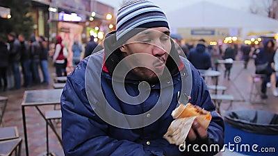 Бездомный голодный парень есть хот-дога призрение Высококалорийная вредная пища, холестерол, тучность сток-видео
