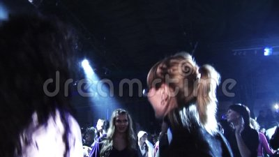 Белокурая девушка в черной верхней части, стеклах танцует на партии в ночном клубе среди других людей Фары толпа сток-видео
