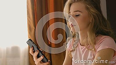 Белокурая женщина сидя на кровати, держа ее телефон в руках и беседуя для того чтобы услышать друзей в розовой пижаме видеоматериал