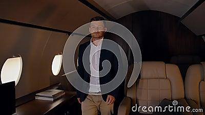 Бизнесмен уверенно и эпиально ходит по частным самолетам сток-видео