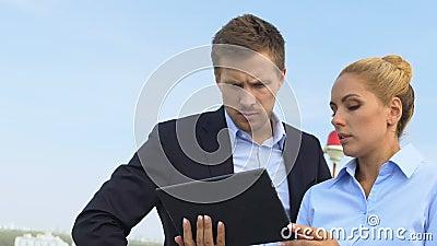 Бизнес-партнеры смотрят на планшет, обсуждают важные проекты на открытом воздухе видеоматериал