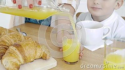 Близкие женские руки, вливающие апельсиновый сок в стекло Завтрак сток-видео