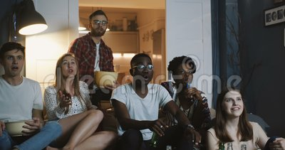 Близкие молодые друзья смотрят спортивную игру дома по телевизору, чувствуют себя эмоционально и разочаровываются, поддерживая вм акции видеоматериалы