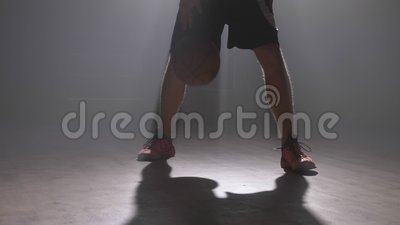 Близкий отснятый видеоматериал ног ` s баскетболиста играя с шариком в темной туманной комнате с дымом акции видеоматериалы
