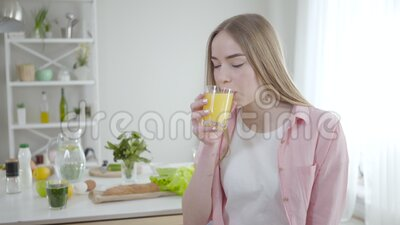 блондинка-кавказка пьет апельсиновый сок и улыбается перед камерой Портрет подходящей красивой девушки, наслаждающейся вкусом акции видеоматериалы