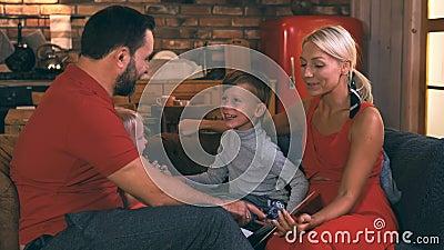 Большая, красивая, дружелюбная семья проводит вечер, читая им книгу Они очень веселые Они смеются и видеоматериал