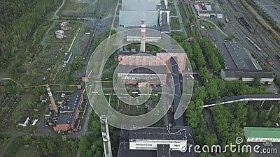 Большое промышленное имущество с работая дымовыми трубами и старыми красными зданиями около вида с воздуха леса сток-видео