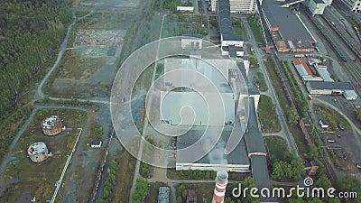 Большое промышленное имущество с работая дымовыми трубами и старыми красными зданиями около вида с воздуха леса видеоматериал