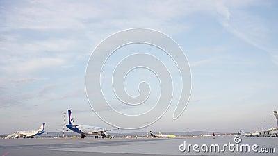 Большой белый самолет пассажирского самолета на взлётно-посадочная дорожка на авиапорте на солнечный день Плоскость на взлётно-по сток-видео