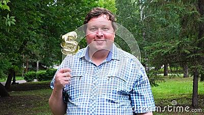 Большой человек держа золотой воздушный шар делая 5 номеров на открытом воздухе 5-ая партия торжества годовщины сток-видео