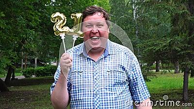 Большой человек держа золотые воздушные шары делая 21 номер на открытом воздухе 21th партия торжества годовщины акции видеоматериалы