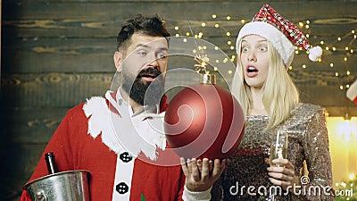 Бородатый человек в костюме и белокурой девушке santa с удивленными сторонами держа в их руках горящей бомбы ново видеоматериал