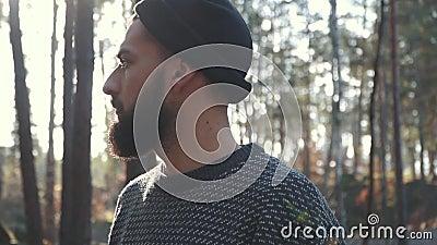 Бородатый человек в лесе смотря далеко вперед Зверский небритый парень в лесе видеоматериал