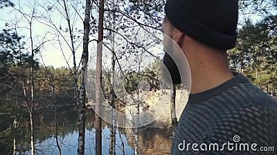 Бородатый человек в лесе смотря далеко вперед Человек с положением оси на скале сток-видео