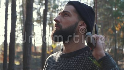 Бородатый человек с осью на его плече смотря далеко вперед Зверский небритый парень с осью в лесе видеоматериал