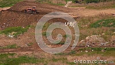 Бульдозер выравнивает насыпь земли видеоматериал