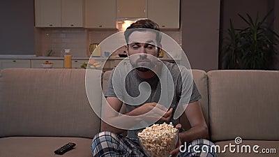 ванта сидит вахты tv софы Он ест попкорн Гай hs оно в стеклянном шаре Он сконцентрирован на наблюдать Он смотрит сток-видео
