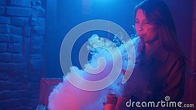 Вапоризатор молодой женщины куря в клубе на красочном свете акции видеоматериалы