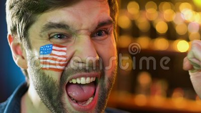 Вентилятор американского футбола с флагом на щеке радуясь любимая победа команды, лига сток-видео
