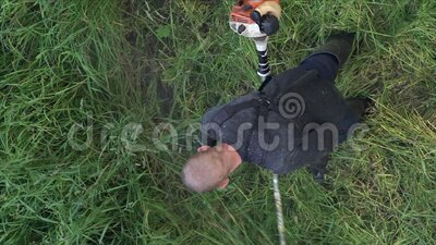 Вертикальный садовник режет траву в летнем саду, используя ручной газонный триммер видеоматериал