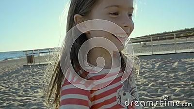 Веселая малая девушка бежит прочь, останавливает, и поворачивает вокруг на берег моря, на заход солнца в slo-mo акции видеоматериалы