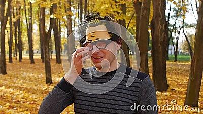 Ветвь ударила глаз неудовлетворенного человека в маске в парке осени Смешной момент акции видеоматериалы