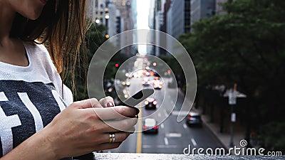 Взгляд конца-вверх молодой женщины используя smartphone, стоя на мосте около дороги движения в Нью-Йорке, Америка акции видеоматериалы