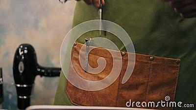 Взгляд крупного плана мужского ` s парикмахера вручает устанавливать штыри волос или barrette к карманн в его рисберме пока подго сток-видео
