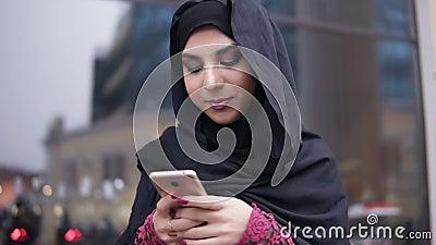 Взгляд крупного плана hijab молодой привлекательной женщины нося стоя в улице, печатая сообщение на ее мобильном телефоне видеоматериал