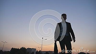 Взгляд низкого угла молодого бизнесмена в официально черном костюме смотря его вахту и ход с его портфелем на городе видеоматериал