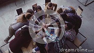 Взгляд сверху команды дела работая на офисе Молодая смешанная группа лицо одной расы людей кладет ладонь совместно на центр Медле