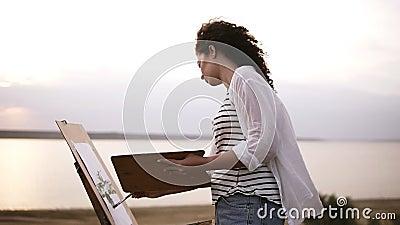 Взгляд со стороны симпатичной женщины рисуя outdoors на луге используя мольберт и палитру Запачканный вид на озеро на видеоматериал