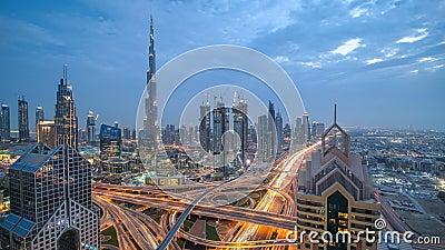 Взгляд на современных небоскребах и занятое выравнивающ день шоссе к timelapse ночи в роскошном городе Дубай, Дубай, объединенном