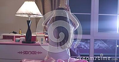 Вид сзади кавказской девушки, надевающей на голову игрушечную корону Школьник играет перед сном Дети, отдых акции видеоматериалы