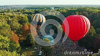 Вид с воздуха на красный горячий воздушный шар взлетает среди деревьев в парке Прекрасное небо и закат акции видеоматериалы
