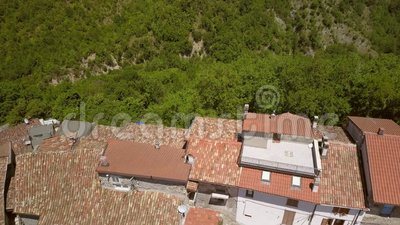 Вид с воздуха на небольшой дом с красной крышей в Петрелло Сальто акции видеоматериалы