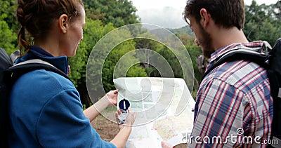 Вид сзади hikers смотря карту с компасом акции видеоматериалы