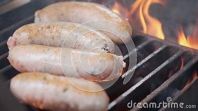 Вкусные сочные сосиски жаря над огнем r r сток-видео