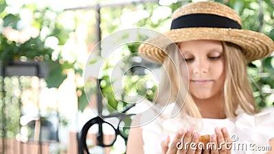 Вначале из фокуса сигналит внутри фокус Портрет милой маленькой девочки держа свеже испеченный кофе испек покрытый с гайками видеоматериал