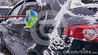 Водитель освобождает автомобиль от крупного плана снега сток-видео