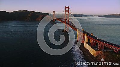 Воздушный вечер над заливом Сан-Франциско в направлении моста 'Золотые ворота' на закате, лодка пересекает мост акции видеоматериалы