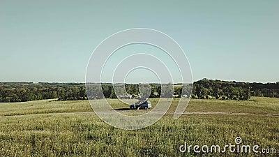 Воздушный полет над автомобилем в поле, дни трутня лета солнечные видеоматериал