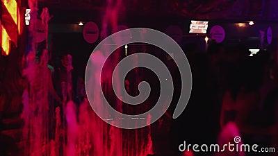 Вода фонтанов под фарами на партии в ночном клубе цветасто люди сток-видео