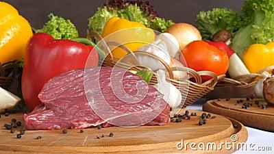 Все еще жизнь с сырцовым мясом свинины и свежими овощами видеоматериал
