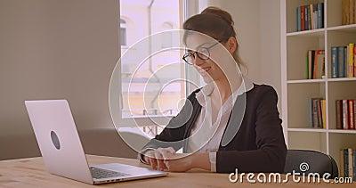 Всход крупного плана молодой милой кавказской коммерсантки имея видео- звонок на ноутбуке говоря жизнерадостно в офисе сток-видео