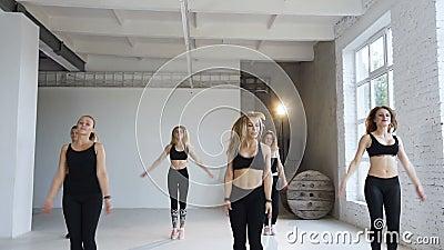 В группе a класса фитнеса 6 молодых женщин в черных костюмах спорт выполните скача тренировки поднимая руки вверх Здорово видеоматериал