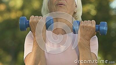 Гантели старухи поднимаясь, усилие разминки, внешняя тренировка, забота тела, здоровье видеоматериал