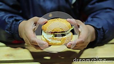 Голодный человек рассматривая бургер Нездоровый обед Быстро-приготовленное питание холестерол тучность акции видеоматериалы