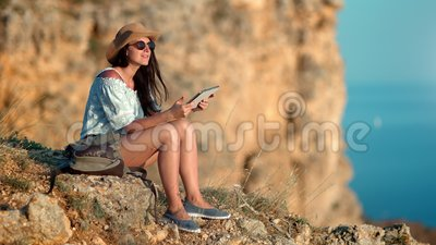 Гора прелестной женщины перемещения хипстера сидя используя ПК планшета на голубой предпосылке моря сток-видео