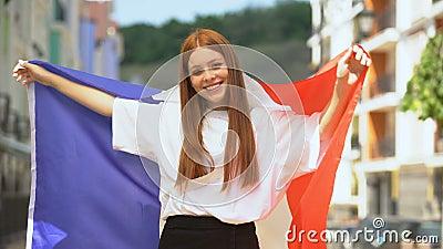 Гордая девушка, размахивая французским флагом и улыбаясь, национальный праздник, спортивный фанат сток-видео